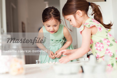 Two young sisters making pastry Stock Photo - Premium Royalty-Free, Image code: 614-06896965