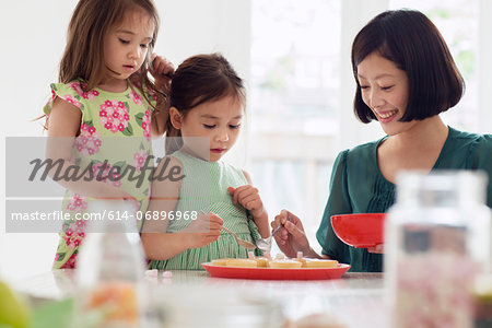 Mother and two daughters spooning topping onto tarts Stock Photo - Premium Royalty-Free, Image code: 614-06896968
