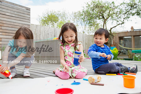 Three young children painting and drawing in garden