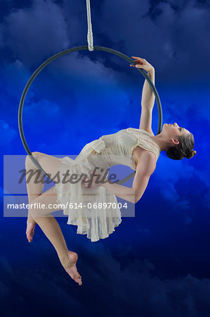 Aerialist performing on hoop against blue background Stock Photo - Premium Royalty-Free, Image code: 614-06897004