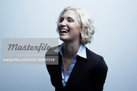 Studio portrait of businesswoman laughing Stock Photo - Premium Royalty-Free, Image code: 614-06897238