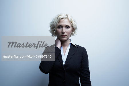 Studio portrait of businesswoman with hand on neck Stock Photo - Premium Royalty-Free, Image code: 614-06897240