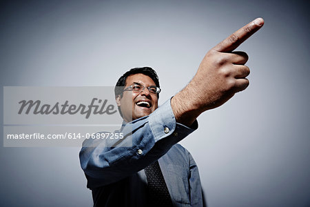 Studio portrait of businessman with exaggerated pointing finger Stock Photo - Premium Royalty-Free, Image code: 614-06897255
