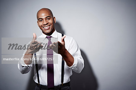 Studio portrait of businessman holding out hands Stock Photo - Premium Royalty-Free, Image code: 614-06897257