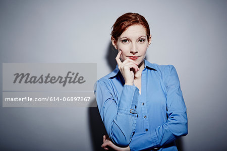 Studio portrait of young woman with hand on chin Stock Photo - Premium Royalty-Free, Image code: 614-06897267
