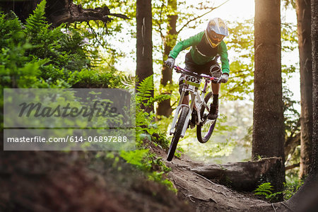 Mountain biker riding through woods Stock Photo - Premium Royalty-Free, Image code: 614-06897288