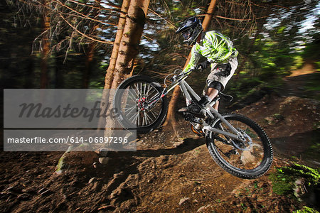 Mountain biker mid air above forest path Stock Photo - Premium Royalty-Free, Image code: 614-06897296