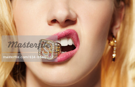 Close up of young woman with diamond ring in her mouth Stock Photo - Premium Royalty-Free, Image code: 614-06897312