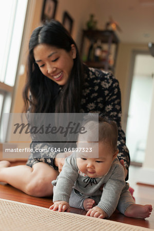 Baby girl sitting on floor with mother Stock Photo - Premium Royalty-Free, Image code: 614-06897323