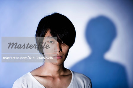 Close up studio portrait of young man in front of blue background Stock Photo - Premium Royalty-Free, Image code: 614-06897340