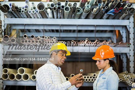 Two warehouse workers looking at copper pipe Stock Photo - Premium Royalty-Free, Image code: 614-06897362