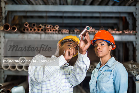 Two warehouse workers looking at copper pipe Stock Photo - Premium Royalty-Free, Image code: 614-06897363
