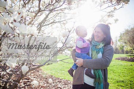 Portrait of baby girl and grandmother next to magnolia blossom Stock Photo - Premium Royalty-Free, Image code: 614-06897399