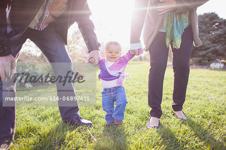 Grandparents walking granddaughter in park Stock Photo - Premium Royalty-Free, Image code: 614-06897411