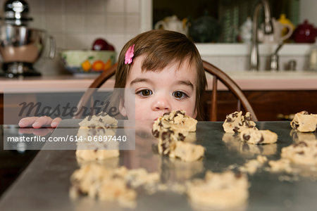 Close up portrait of young female toddler looking at currant cakes Stock Photo - Premium Royalty-Free, Image code: 614-06897440