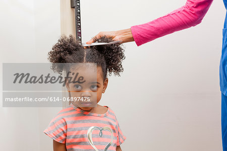 Nurse measuring height of young patient Stock Photo - Premium Royalty-Free, Image code: 614-06897475