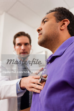 Mid adult doctor using stethoscope on patient Stock Photo - Premium Royalty-Free, Image code: 614-06897483