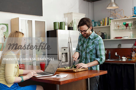 Woman on laptop computer, man chopping vegetables Stock Photo - Premium Royalty-Free, Image code: 614-06897561