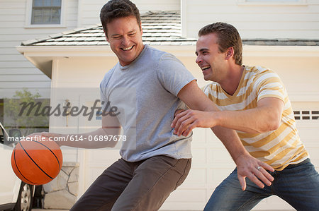 Father and adult son playing basketball Stock Photo - Premium Royalty-Free, Image code: 614-06897678