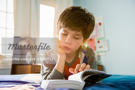 Boy lying on bed reading book Stock Photo - Premium Royalty-Free, Image code: 614-06897712