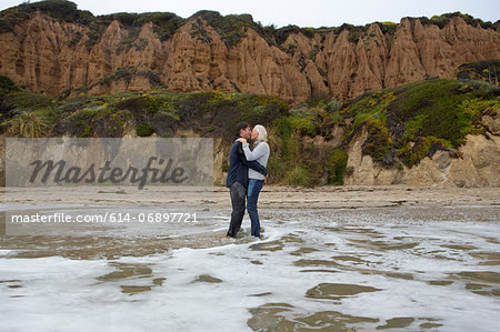 Mature couple standing in sea kissing Stock Photo - Premium Royalty-Free, Image code: 614-06897721