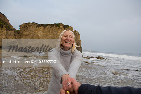 Mature couple holding hands on beach Stock Photo - Premium Royalty-Free, Image code: 614-06897723
