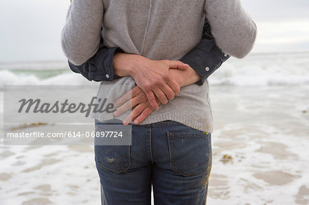 Mature couple embracing on beach, mid section Stock Photo - Premium Royalty-Free, Image code: 614-06897724