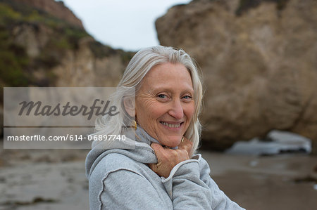 Mature woman wearing grey sweater on beach, smiling Stock Photo - Premium Royalty-Free, Image code: 614-06897740