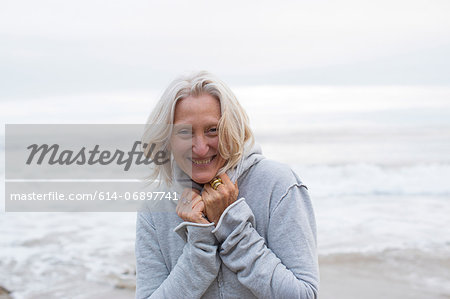 Mature woman wearing grey sweater on beach, smiling Stock Photo - Premium Royalty-Free, Image code: 614-06897741