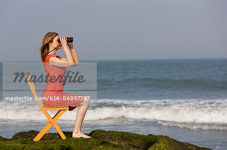 Mature woman sitting on chair on beach with binoculars Stock Photo - Premium Royalty-Free, Image code: 614-06897787