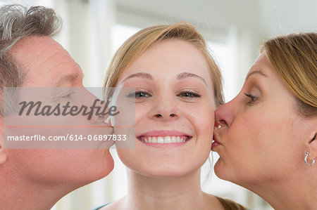 Mother and father kissing teenage daughter on cheek Stock Photo - Premium Royalty-Free, Image code: 614-06897833