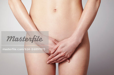 Young woman covering herself with hands Stock Photo - Premium Royalty-Free, Image code: 614-06897873