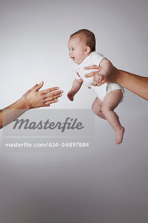 Parents passing baby daughter to each other Stock Photo - Premium Royalty-Free, Image code: 614-06897884
