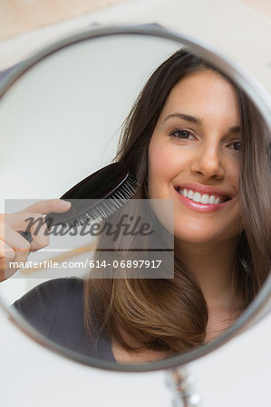 Young woman brushing hair in mirror Stock Photo - Premium Royalty-Free, Image code: 614-06897917