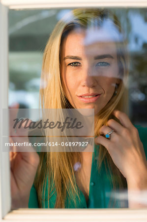 Portrait of young woman looking through window, hand in hair Stock Photo - Premium Royalty-Free, Image code: 614-06897927