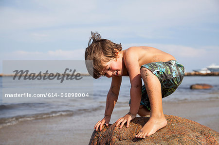 Boy crouching on rock on beach Stock Photo - Premium Royalty-Free, Image code: 614-06898004