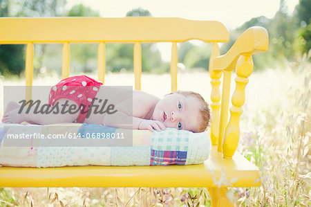 Newborn baby girl lying on yellow bench in field Stock Photo - Premium Royalty-Free, Image code: 614-06898011