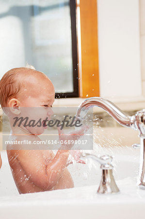 Baby girl playing with water in tap Stock Photo - Premium Royalty-Free, Image code: 614-06898017