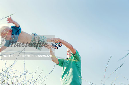Father spinning son in field, low angle Stock Photo - Premium Royalty-Free, Image code: 614-06898025