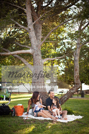 Family with two children sitting on picnic blanket under tree Stock Photo - Premium Royalty-Free, Image code: 614-06898058