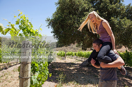 Young couple in vineyard, man giving woman piggy back Stock Photo - Premium Royalty-Free, Image code: 614-06898135