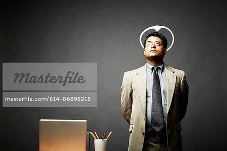 Man with hands behind back looking angelic Stock Photo - Premium Royalty-Free, Image code: 614-06898218