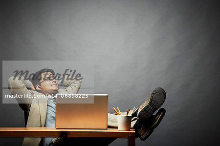 Man relaxing with feet up on table Stock Photo - Premium Royalty-Free, Image code: 614-06898223