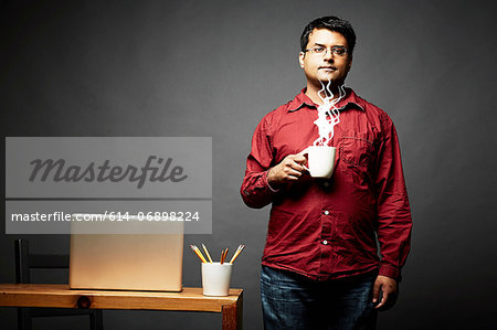 Man holding cup of steaming hot beverage Stock Photo - Premium Royalty-Free, Image code: 614-06898224