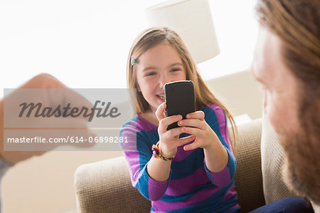 Daughter photographing father with smartphone Stock Photo - Premium Royalty-Free, Image code: 614-06898281