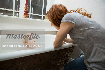 Mother smiling at child in bathtub Stock Photo - Premium Royalty-Free, Image code: 614-06898424
