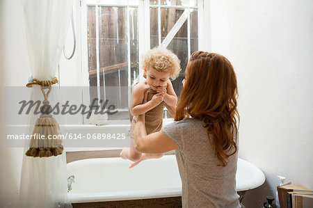 Mother lifting child from bathtub Stock Photo - Premium Royalty-Free, Image code: 614-06898425