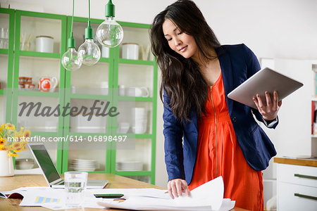 Woman with digital tablet looking through paperwork Stock Photo - Premium Royalty-Free, Image code: 614-06898497