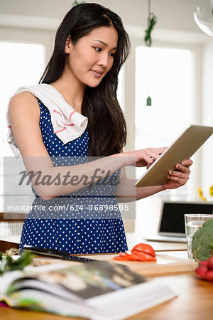 Woman with tea towel over shoulder using digital tablet Stock Photo - Premium Royalty-Free, Image code: 614-06898505
