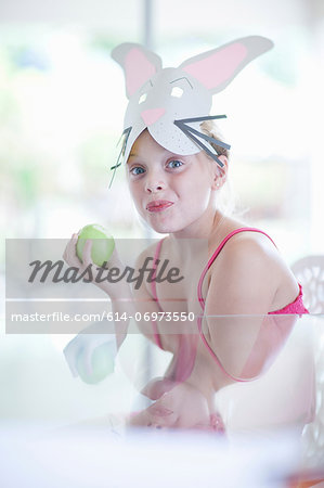 Girl in rabbit costume eating apple Stock Photo - Premium Royalty-Free, Image code: 614-06973550